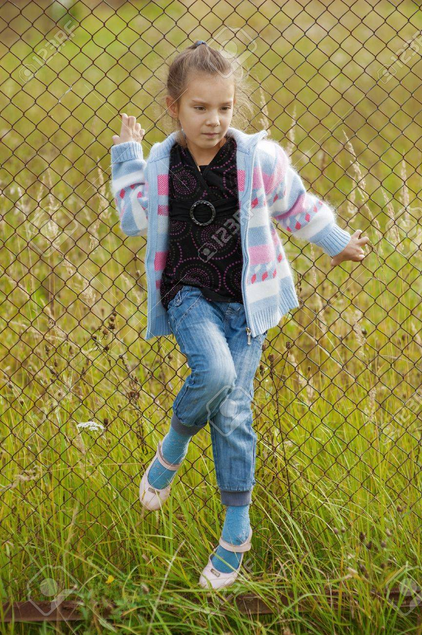 Beautiful little girl on metal grid in old grassy park Stock Photo - 16639238