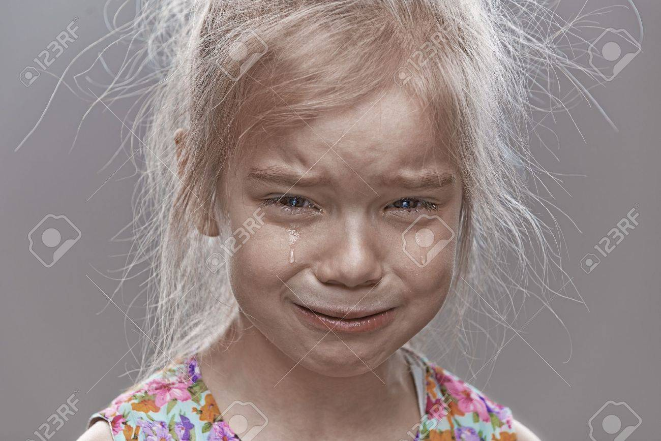 Beautiful sad little girl crying, on gray background. Stock Photo - 19536804