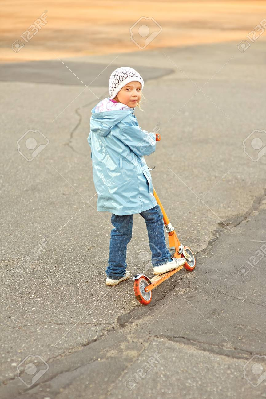 Little beautiful smiling girl riding scooter on pavement. Stock Photo - 19804055