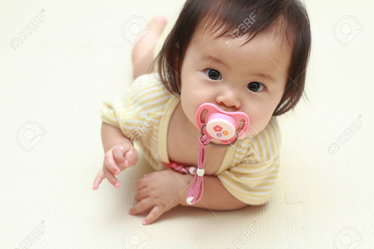 Japanese baby girl sucking on a pacifier (0 year old) - 41671715