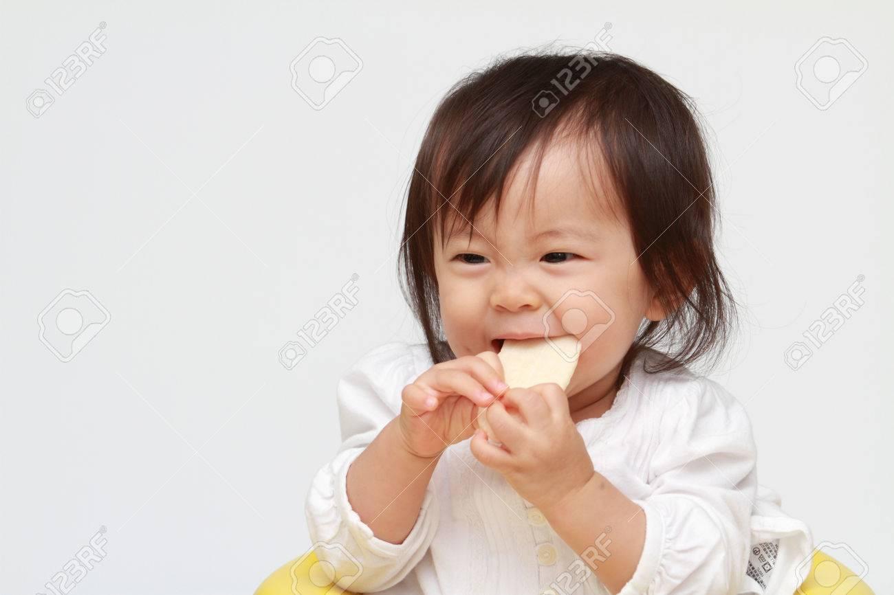 Japanese baby girl eating rice cracker (0 year old) - 47468924