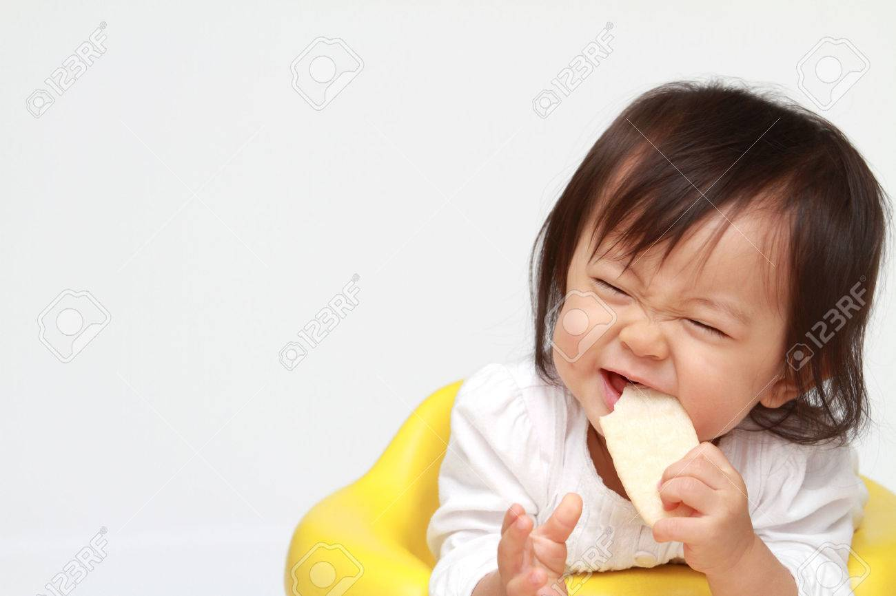 Japanese baby girl eating rice cracker (0 year old) - 47468929