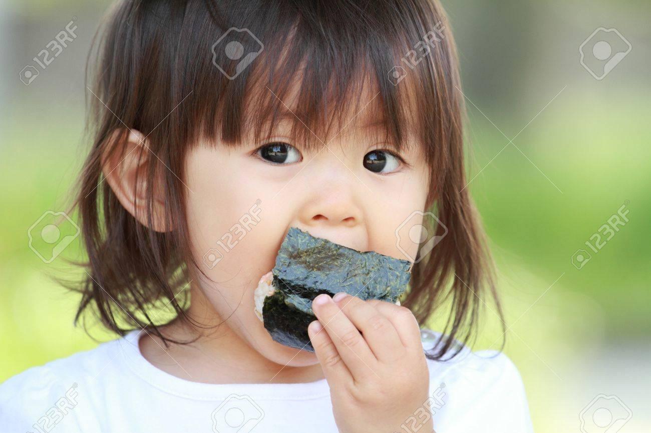 Japanese girl eating rice ball (1 year old) - 57048288