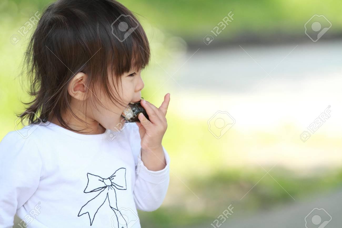 Japanese girl eating rice ball (1 year old) - 57048292