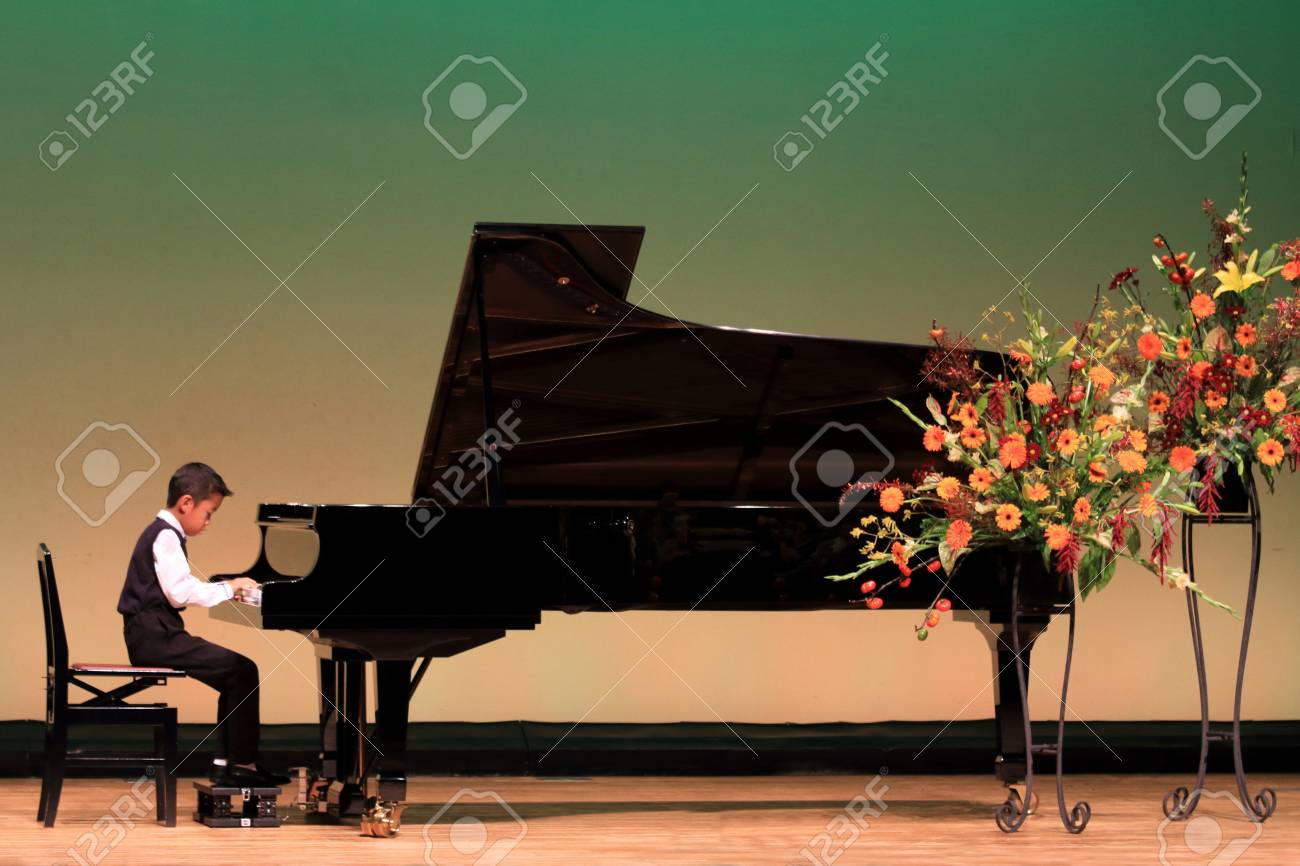 Japanese boy playing piano on stage (second grade at elementary school) - 89706106