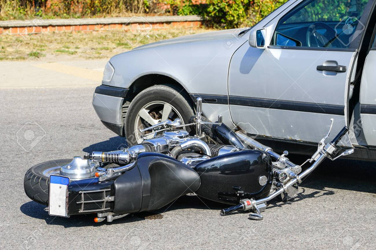 traffic accident, motorcycle collision with a car on city street, overturned motorcycle - 130354213