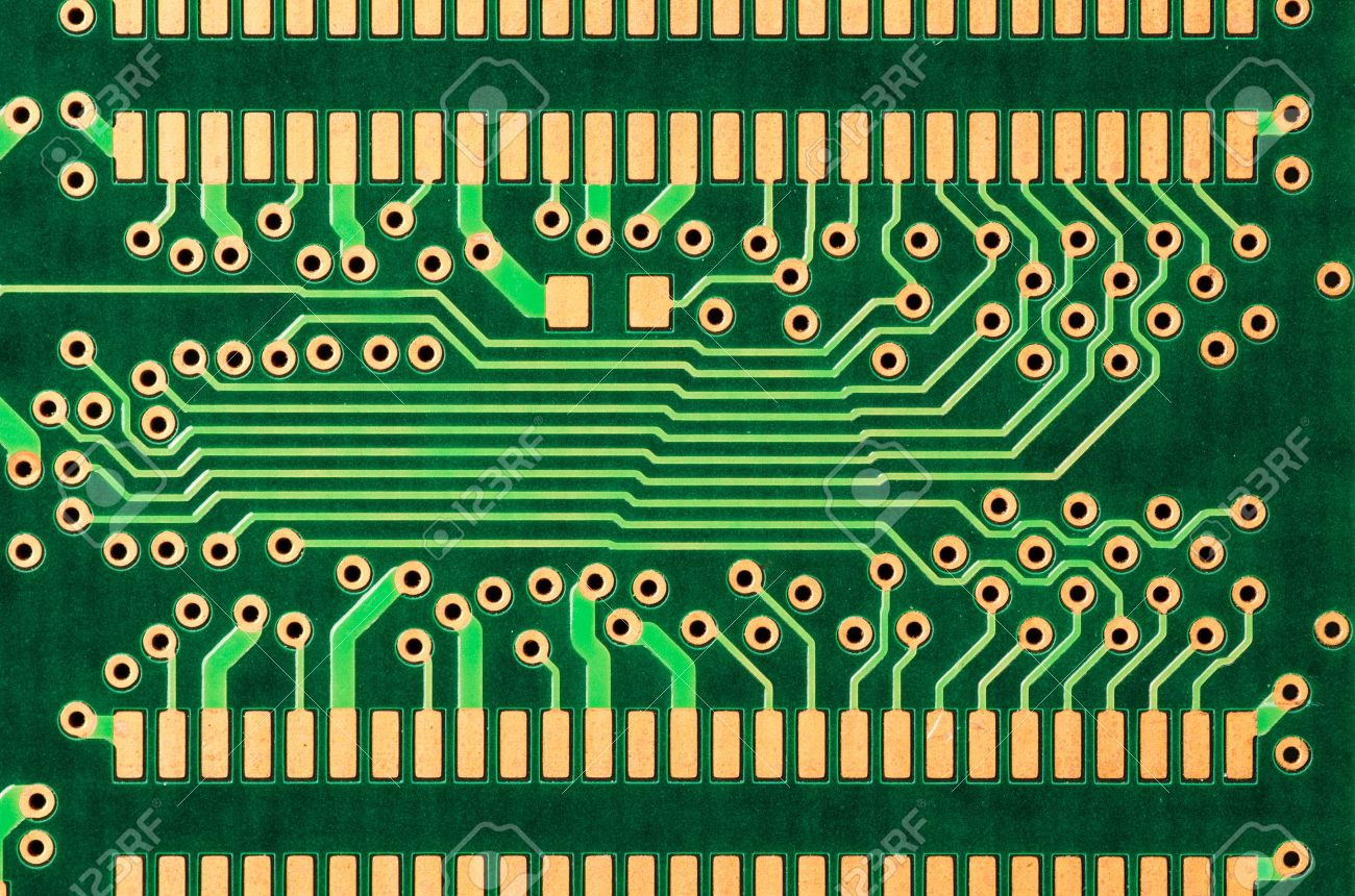 a closeup of a printed circuit board with gold traces stock photo