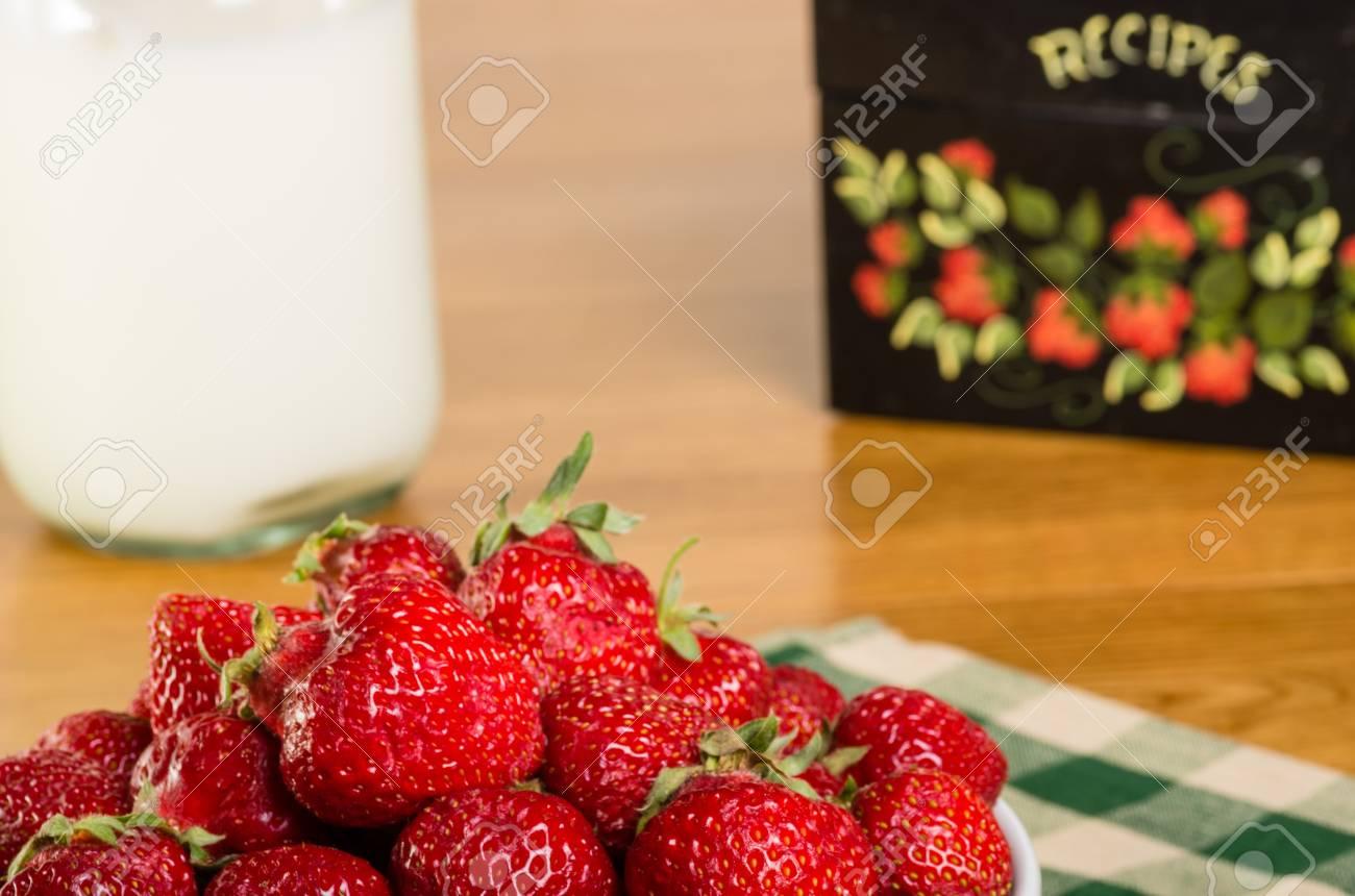 Un Tazón De Fresas Frescas Con Una Caja De Recetas Y Una Botella De Leche