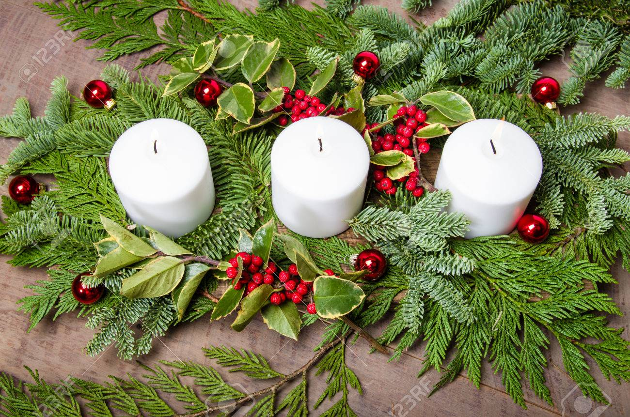 An Evergreen Christmas.An Evergreen Christmas Centerpiece With Three White Candles And
