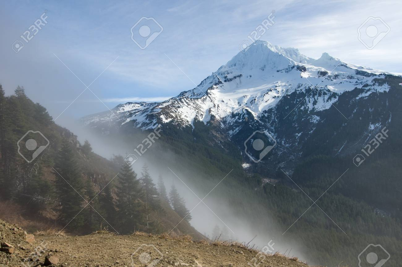 Fog rolling over the pass near snow capped Mt Hood - 82795554