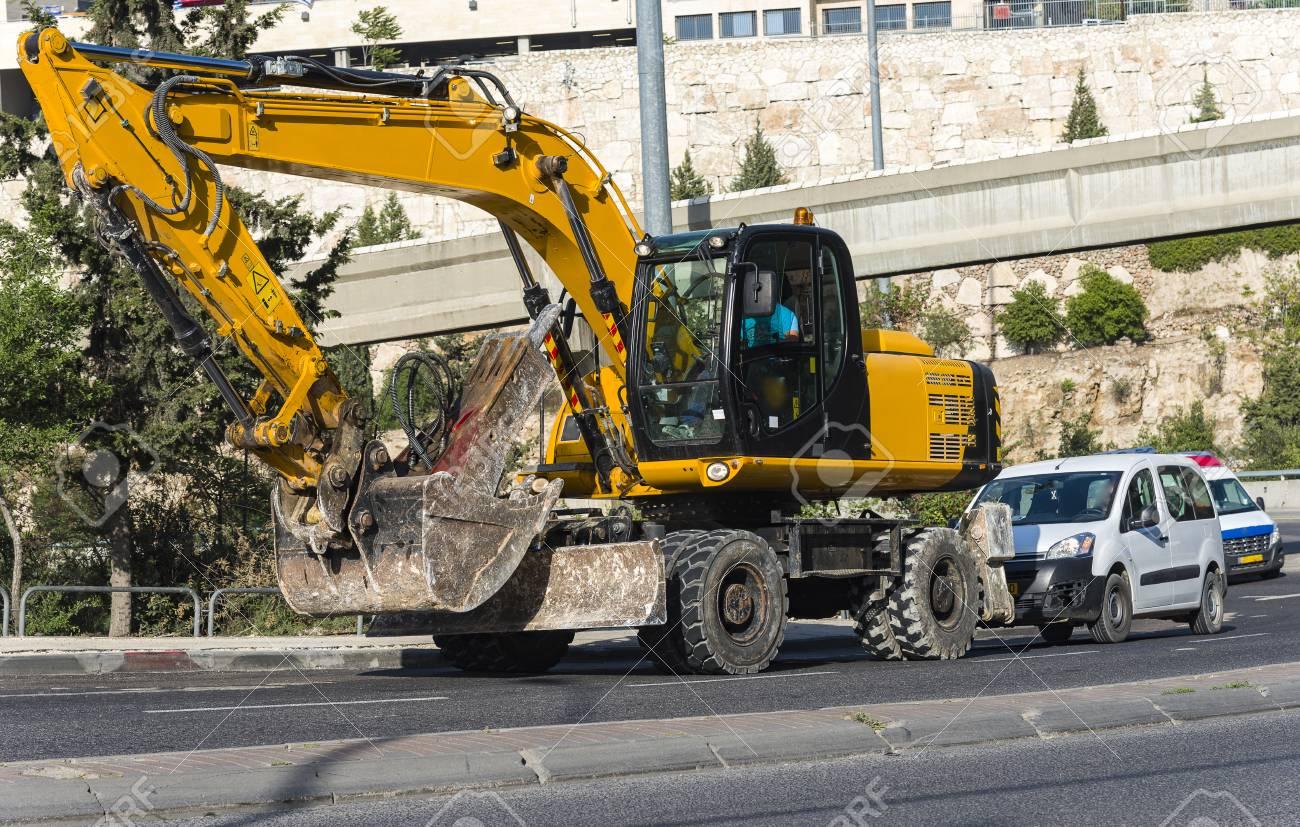 excavator loader machine with risen boom construction site yellow