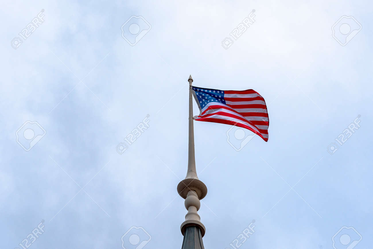 American flag waving in blue sky. American flag at the top. - 159417904