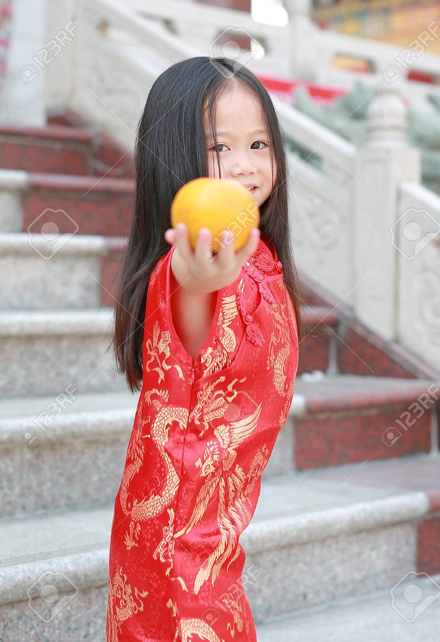 70dd42eeb ... Chinese new year concept. Cute asian kid girl in Traditional Chinese  dress with holding sacred Orange at chinese temple in