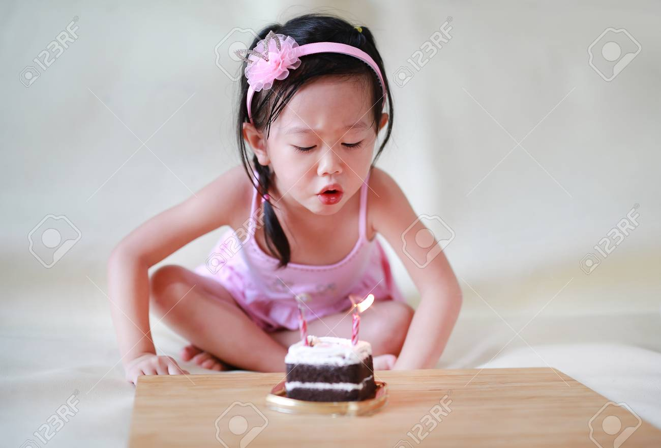 Cute Little Girl Blowing Small Birthday Candles On Cake 2 Years