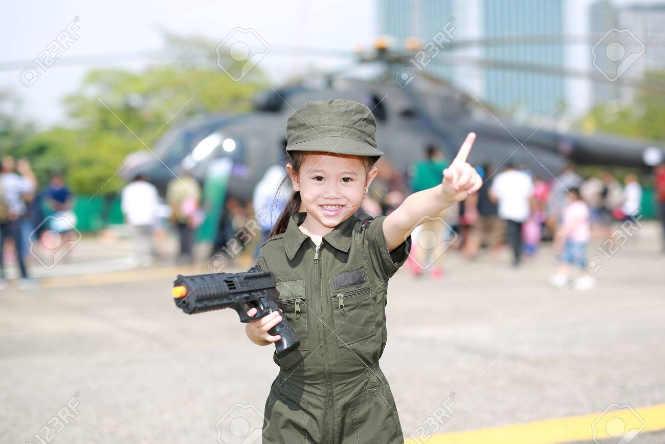 Little Asian child girl in pilot soldier suit costume with holding..