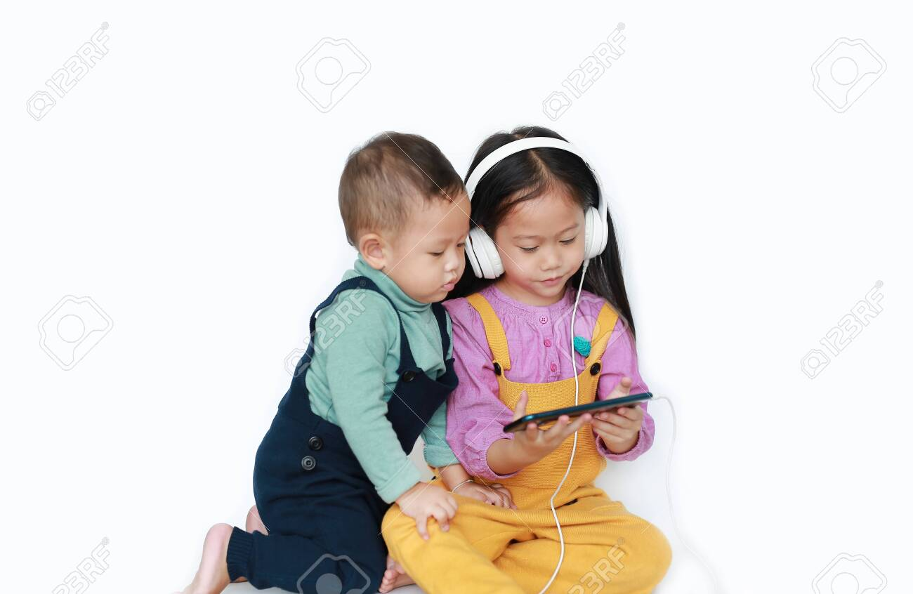 Adorable Asian older sister and little brother sharing to enjoys listening music with headphones by smartphone isolated over white background. Sharing concept. - 126559313