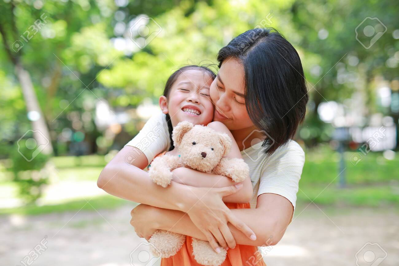 Portrait of happy Asian mother cuddle daughter and hugging teddy bear doll in the garden. Mom and child girl with love and relationship concept. - 128805700