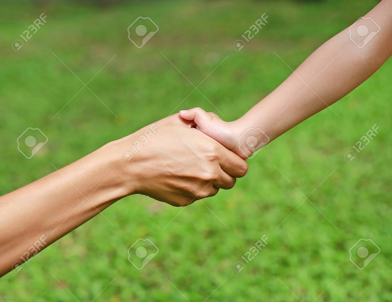 Close-up of mother and child holding by hands - 129398583