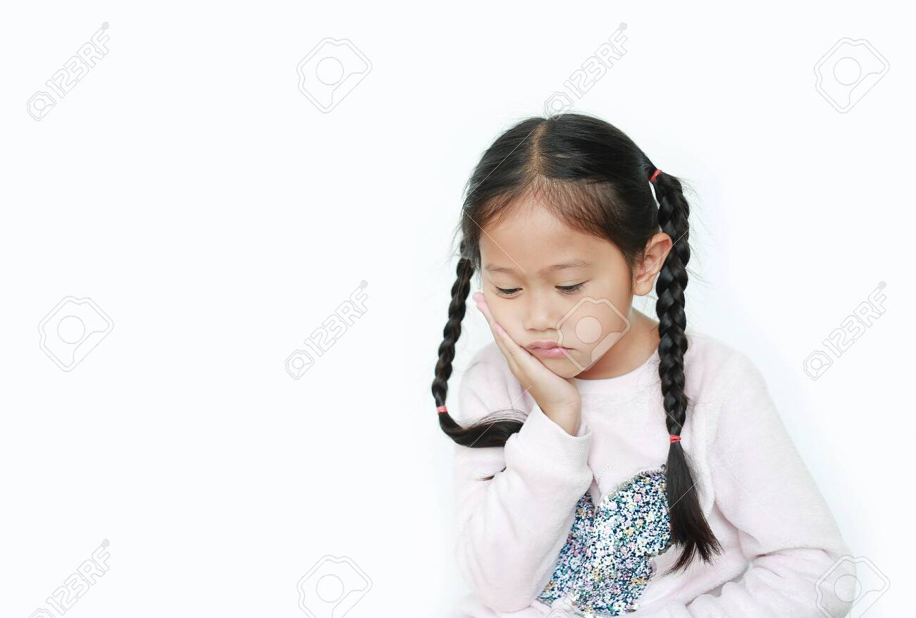 Serious and sad Asian little child girl with posture her hand on cheek isolated over white background. - 136810326