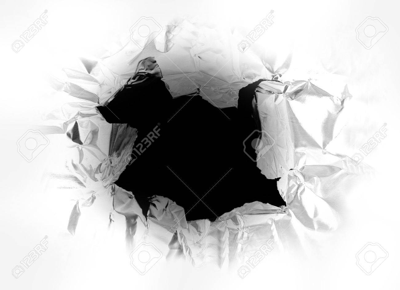 hole torn in a piece of metal, with light shining thru Stock Photo - 3620459