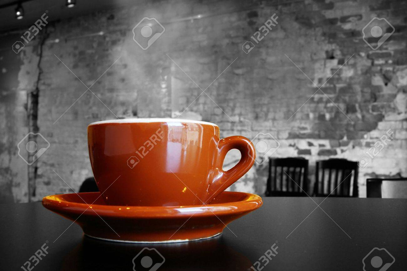 cappuccino coffee cup and saucer in a brick cafe interior stock