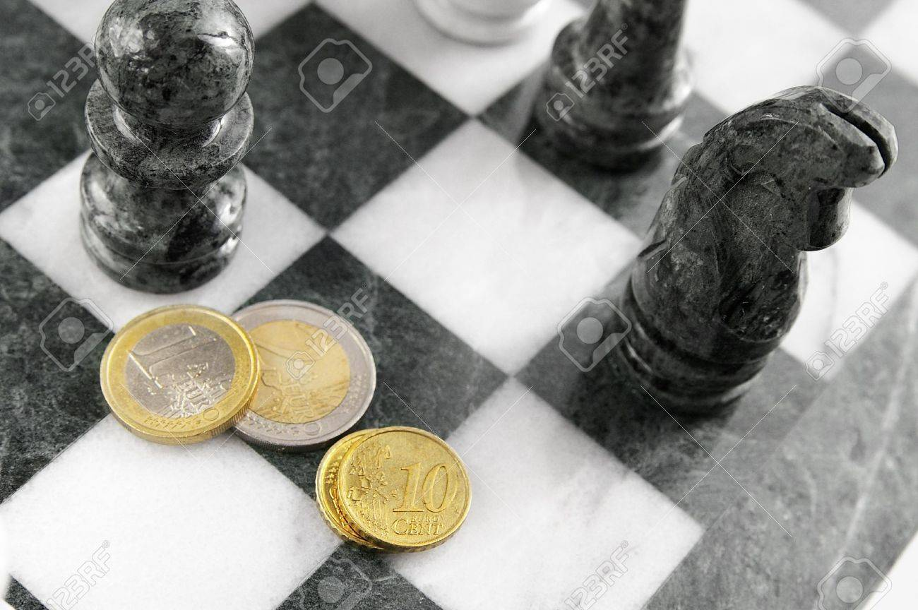 Euro coins on a chess board, top view