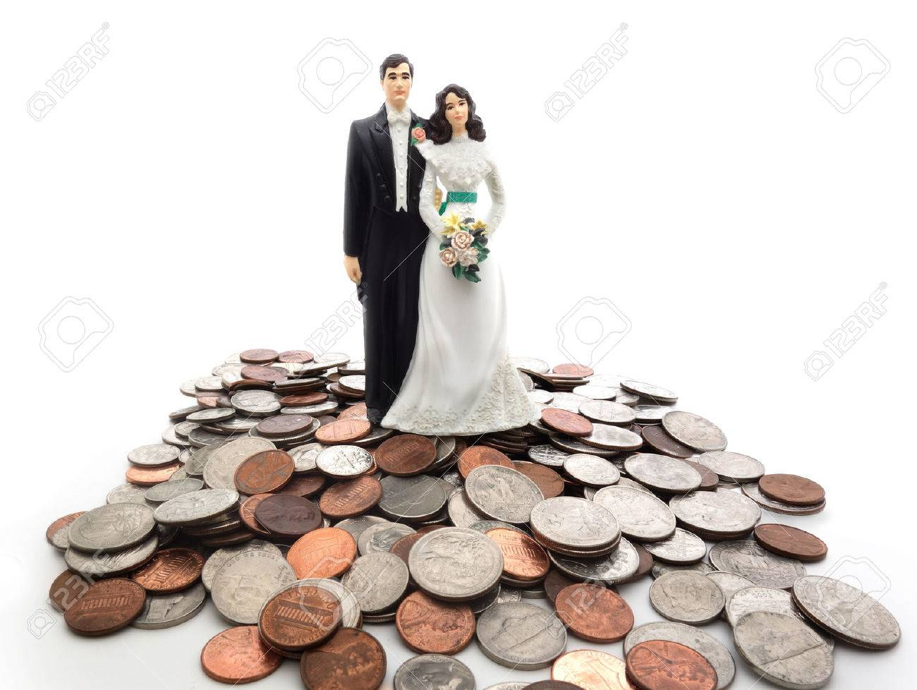 Plastic wedding couple on a pile of coins - money concept - 27699301
