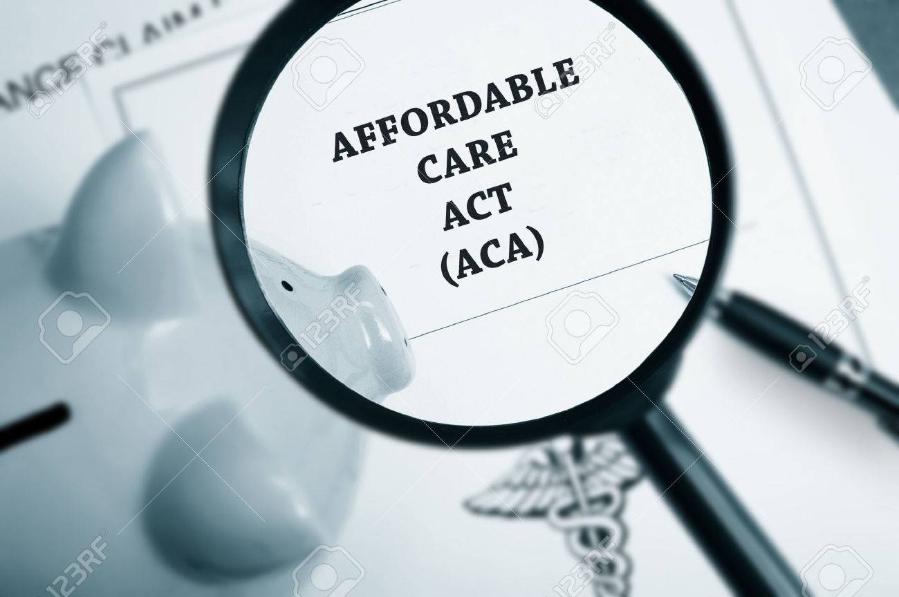 Magnifying glass over Affordable Care Act policy and piggy bank - 33034953