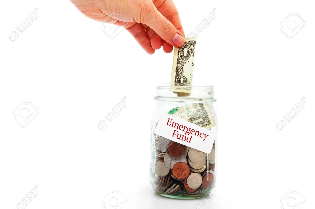 hand putting a money into Emergency Fund jar - Rainy Day fund concept - 33357240