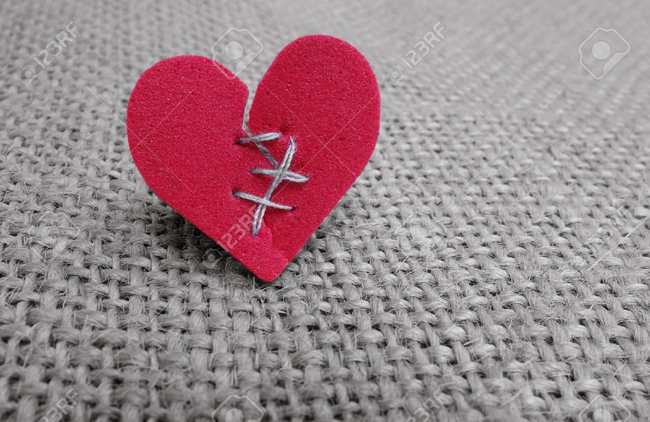 Broken red heart with white thread stitches - 54552069