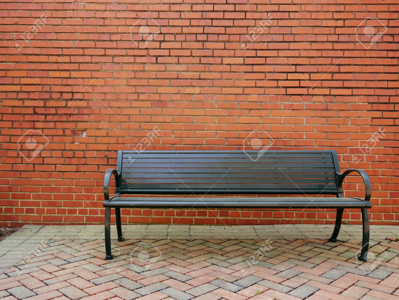 An empty metal park bench in front of a blank brick wall - 169465827