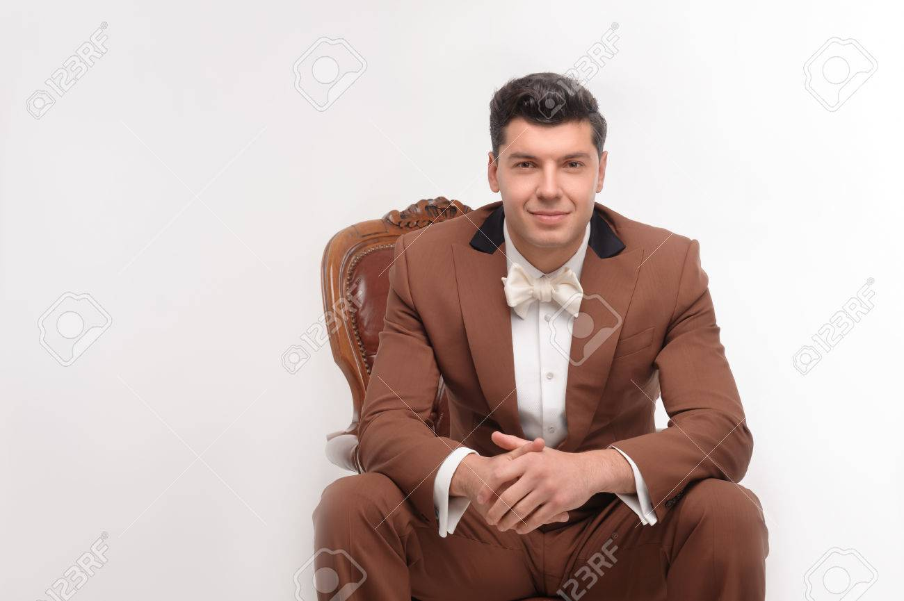 Young Attractive Smiling Man In Brown Suit Sitting In Armchair ...