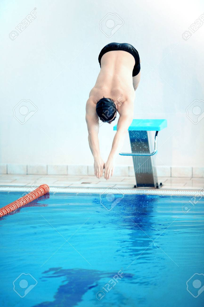 Born To Swim. Ready To Win. Muscular Swimmer Standing On The Diving Board  Ready
