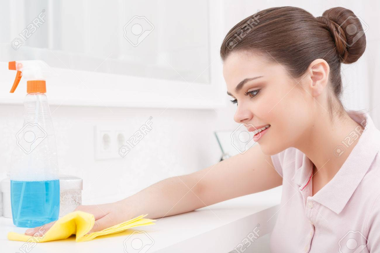 dusting furniture. Pretty Lady Dusting White Furniture Table With Mirror On Her Knees Help Of Yellow Cloth And Mean Washing Background D