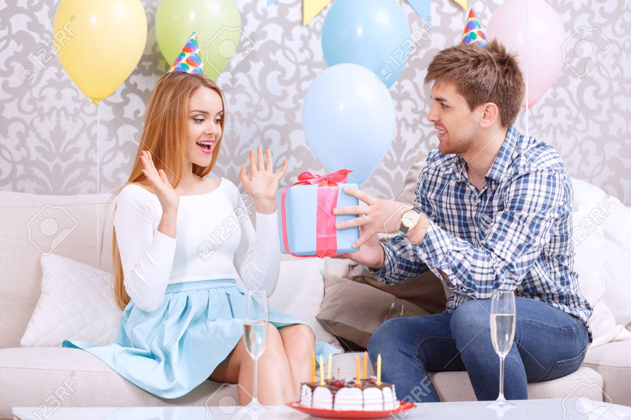 Young Man Presenting A Birthday Gift To His Girl Friend Looking