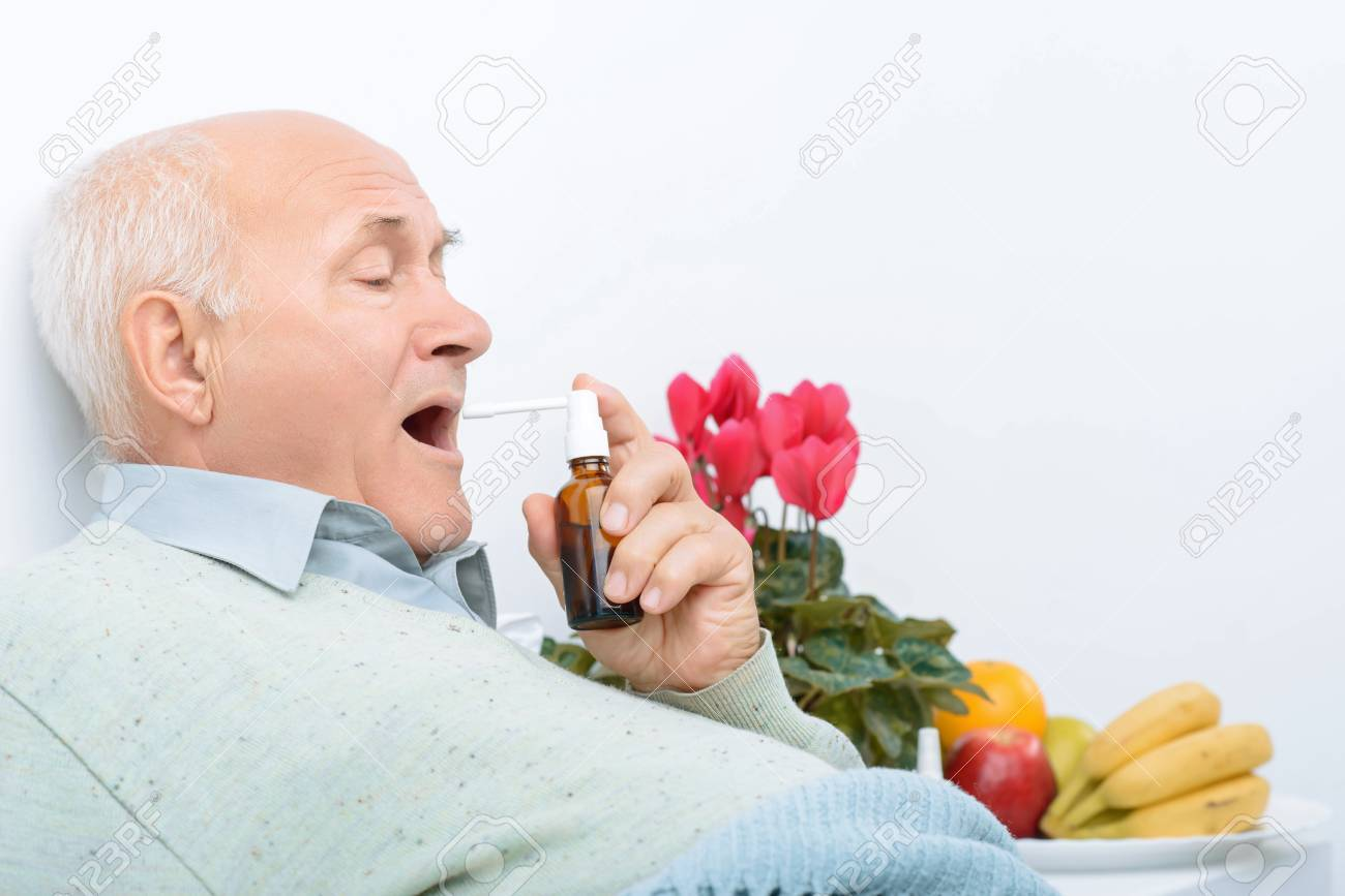Sore throat treatment  Senior aged man lies on hospital bed and