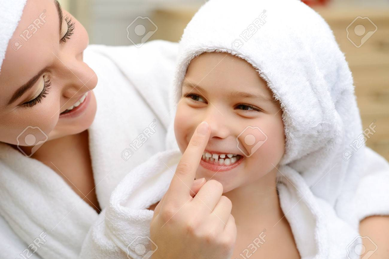 My darling. Close up of pleasant smiling daughter and loving mother having fun together after taking bath - 50044025