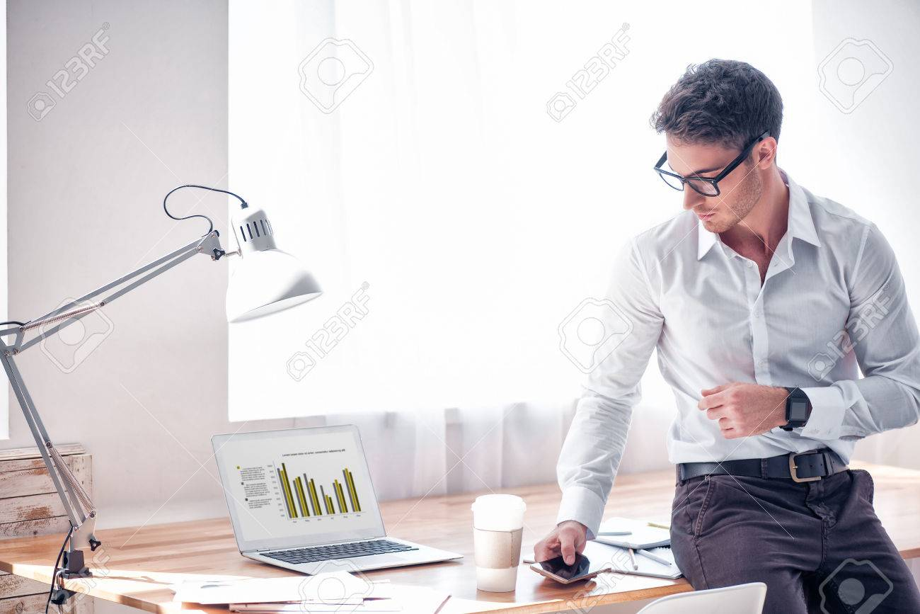 Real professional. Pleasant brutal handsome man leaning on the table and holding cell phone while being involved in work - 57613493