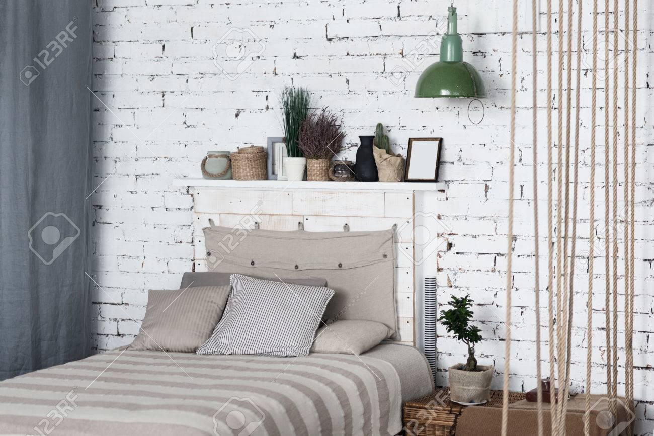 Tutto ciò di cui hai bisogno. Moderna camera da letto con letto  matrimoniale grigia sullo sfondo del muro di mattoni bianchi, di cui sopra  è mensola e ...