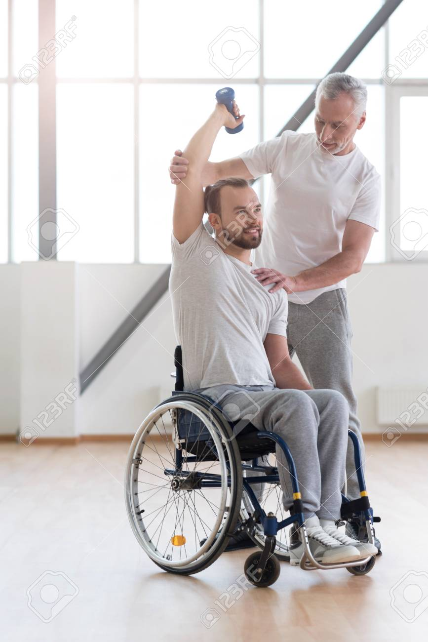 Powerful disabled man exercising with his coach in the gym stock