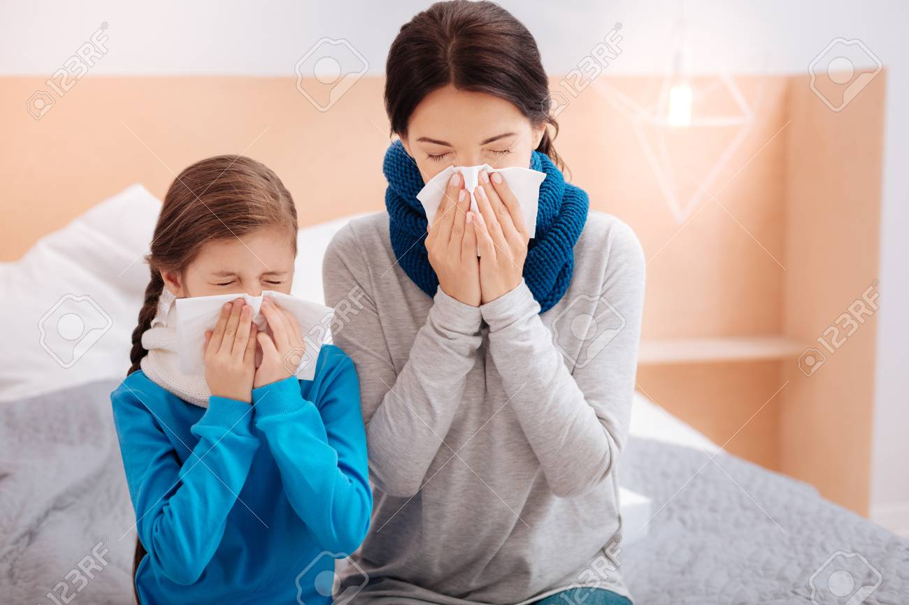 Ill mother and daughter sneezing together - 87880485