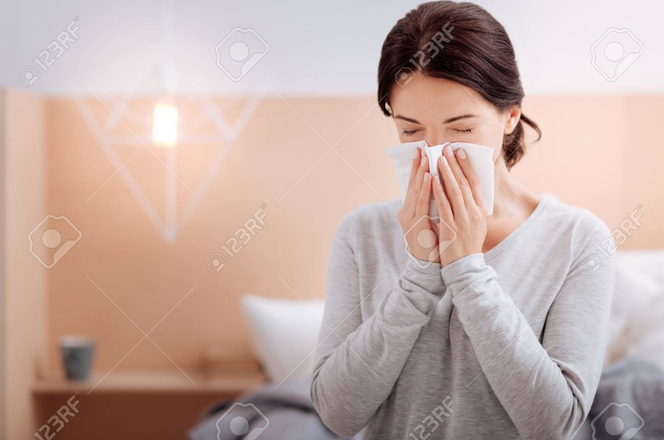 Ill woman sitting at home and sneezing - 87880513