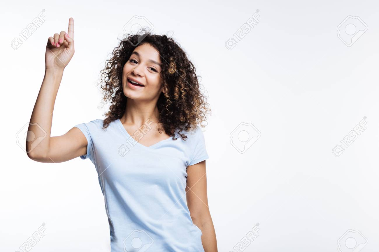Upbeat curly woman pointing up with her finger - 88562848