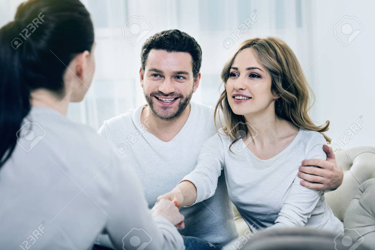 Thanks for help. Beautiful delighted nice woman looking at her therapist and shaking her hand while sitting together with her husband on the sofa - 90711604