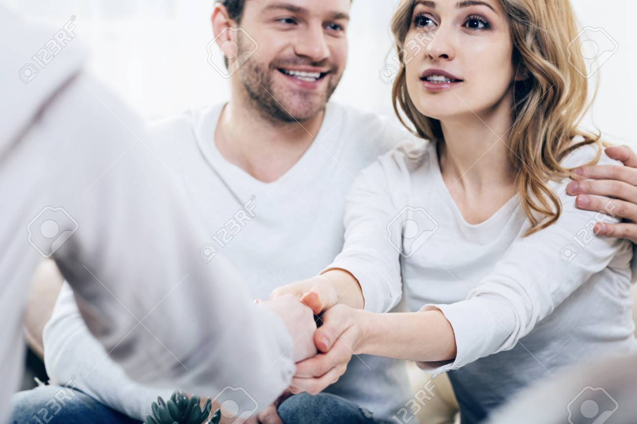 Happy patients. Cheerful positive young woman sitting together with her husband and expressing her gratitude to her therapist while feeling happy - 90503825