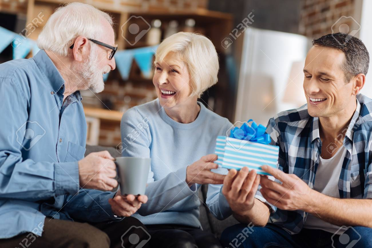 Happy Birthday Upbeat Young Man Sitting On The Sofa Next To His Elderly Parents And