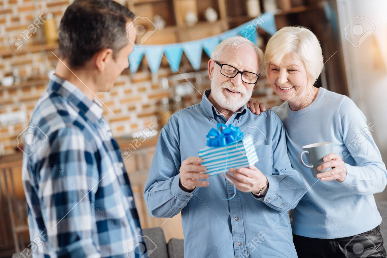 Happy Elderly Man Examining His Birthday Present Having Received It From
