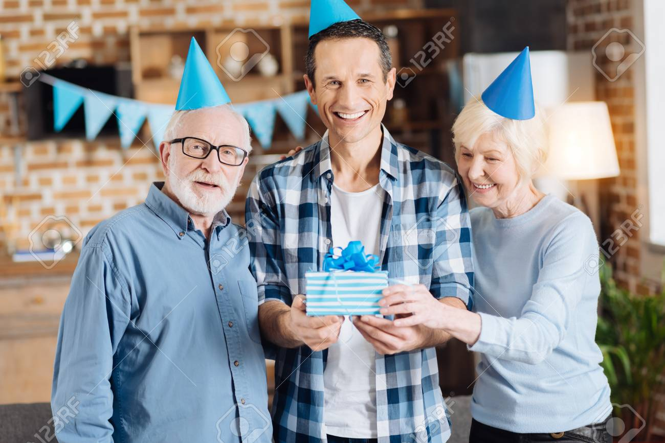 Upbeat Young Man Standing Between His Elderly Parents And Holding Birthday Gift
