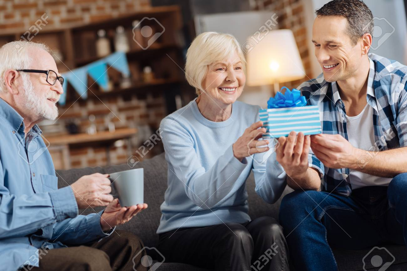 Gift With Love Cheerful Young Man Giving A Birthday Present To His Happy Elderly Mother