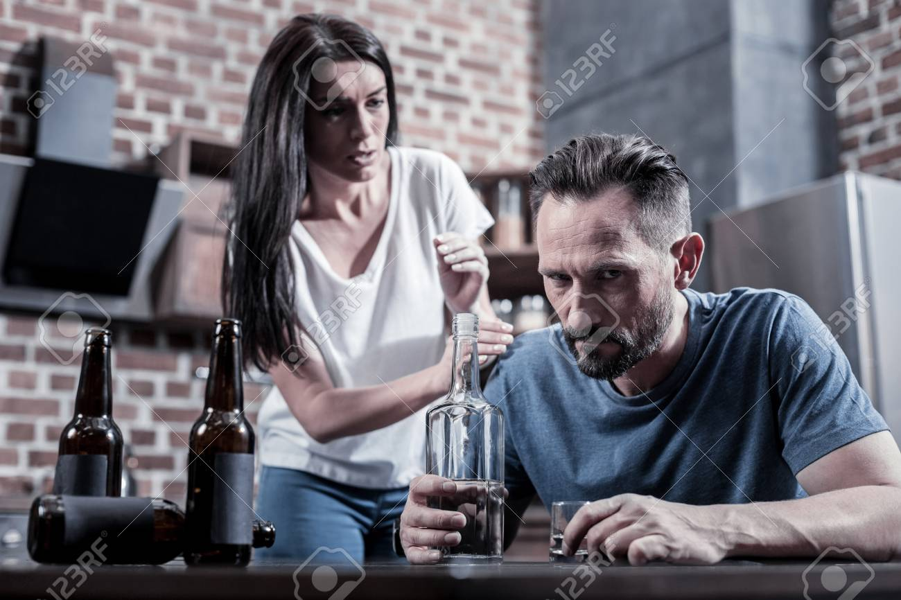 Alcoholic in a family. Brutal bearded sad man sitting in front of the vodka bottle and thinking about his problems while drinking at home - 92763003
